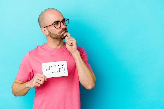 Jonge blanke kale man met een help-plakkaat geïsoleerd op paarse muur opzij kijken met twijfelachtige en sceptische uitdrukking