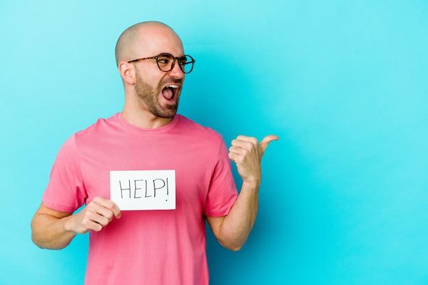 Jonge blanke kale man met een help-plakkaat geïsoleerd op paarse muur wijst met duimvinger weg, lachend en zorgeloos.