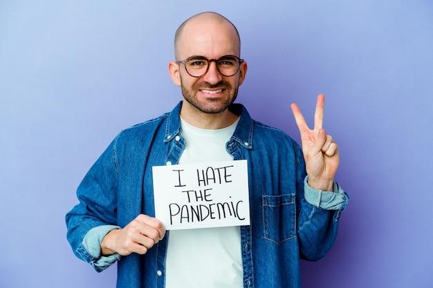 Jonge blanke kale man met een ik haat het pandemische aanplakbiljet dat op blauwe muur wordt geïsoleerd die nummer twee met vingers toont.