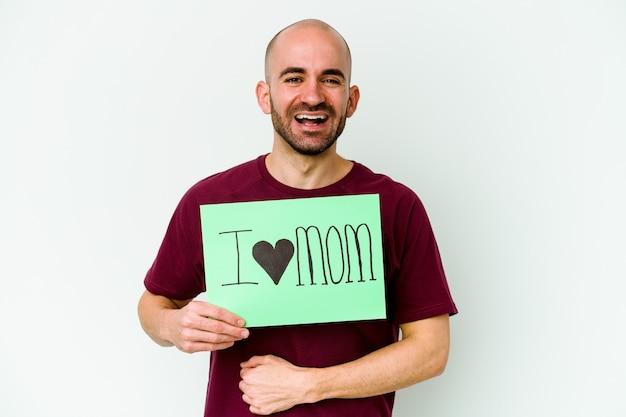 Jonge blanke kale man met een ik hou van moeder aanplakbiljet geïsoleerd op gele muur lachen en plezier maken
