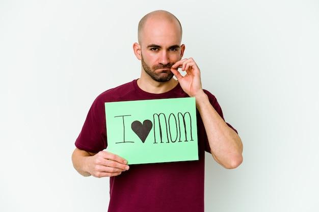 Jonge blanke kale man met een ik hou van moeder aanplakbiljet geïsoleerd op gele muur met vingers op lippen die een geheim bewaren.