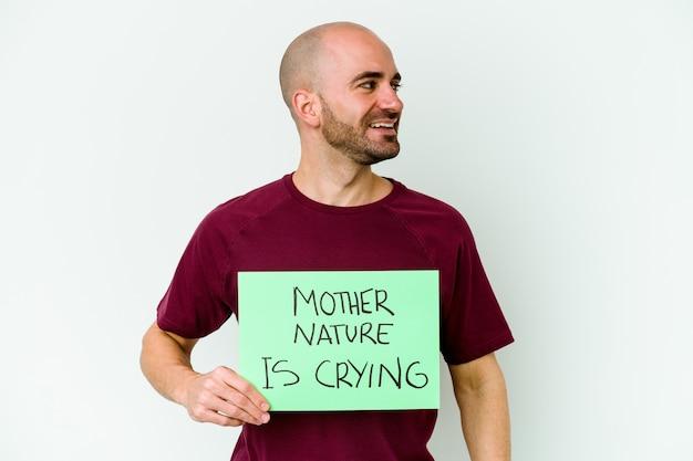 Jonge blanke kale man met een moeder natuur huilen geïsoleerd op een witte muur kijkt opzij glimlachend, vrolijk en aangenaam.