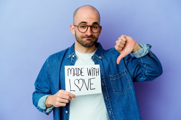 Jonge blanke kale man met een plakkaat gemaakt met liefde geïsoleerd op paarse muur met een afkeer gebaar, duimen naar beneden. meningsverschil concept.