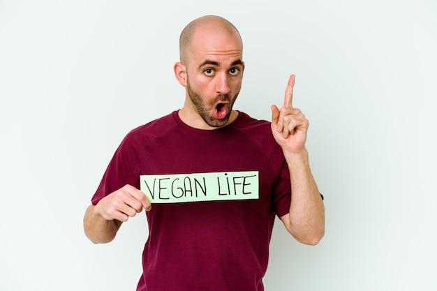 Jonge blanke kale man met een plakkaat veganistisch leven geïsoleerd op paarse achtergrond met een idee, inspiratie concept.