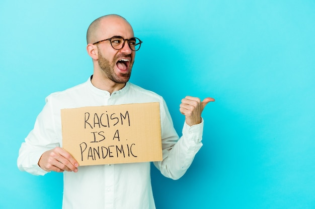 Jonge blanke kale man met een racisme is een pandemie geïsoleerd op een witte muur wijst met duimvinger weg, lachend en zorgeloos.