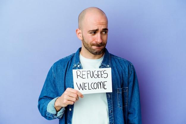 Jonge blanke kale man met een vluchtelingen welkom plakkaat geïsoleerd op blauwe muur verward, twijfelachtig en onzeker.