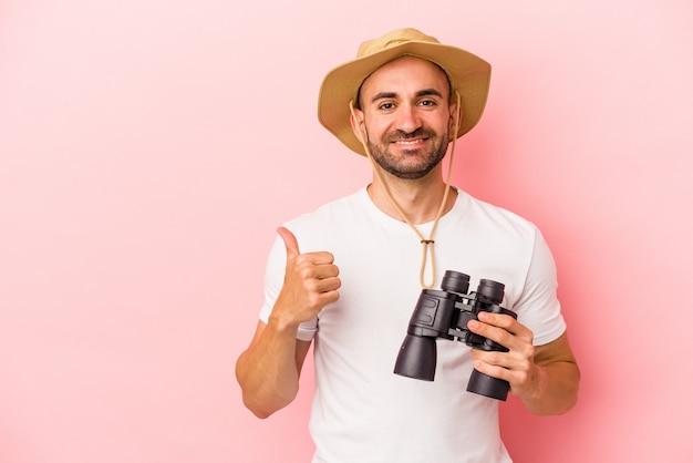 Jonge blanke kale man met verrekijker geïsoleerd op roze achtergrond glimlachend en duim omhoog
