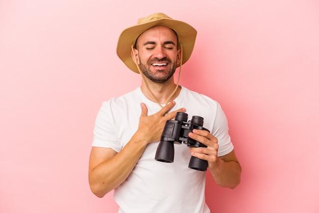 Jonge blanke kale man met verrekijker geïsoleerd op roze achtergrond lacht hardop terwijl hij de hand op de borst houdt.