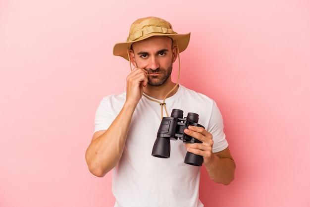 Jonge blanke kale man met verrekijker geïsoleerd op roze achtergrond met vingers op lippen die een geheim houden.