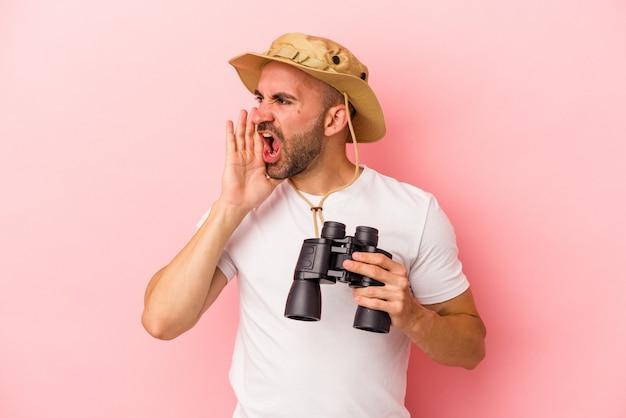 Jonge blanke kale man met verrekijker geïsoleerd op roze achtergrond schreeuwen en houden palm in de buurt van geopende mond.
