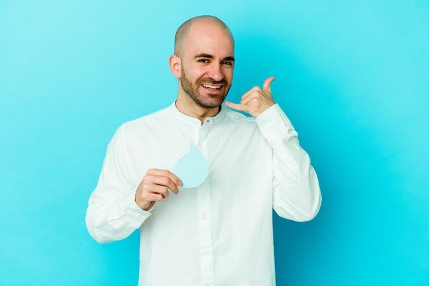Jonge blanke kale man vieren wereld water dag geïsoleerd op blauwe achtergrond met een mobiele telefoongesprek gebaar met vingers.