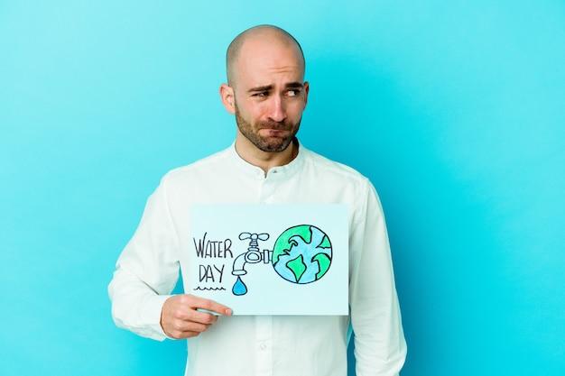 Jonge blanke kale man vieren wereld water dag geïsoleerd op blauwe achtergrond verward