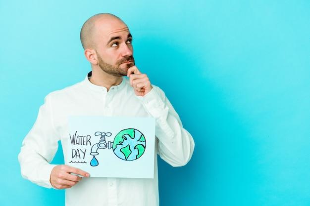 Jonge blanke kale man vieren wereld water dag geïsoleerd op blauwe achtergrond
