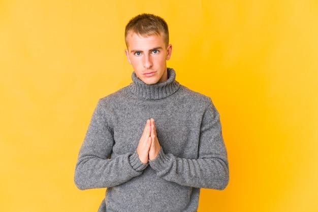 Jonge blanke knappe man bidden, toewijding, religieuze persoon op zoek naar goddelijke inspiratie.