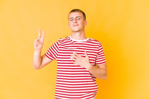 Jonge blanke knappe man die een eed aflegt, hand op de borst legt.