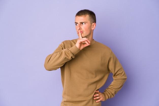 Jonge blanke knappe man die een geheim houdt of om stilte vraagt.