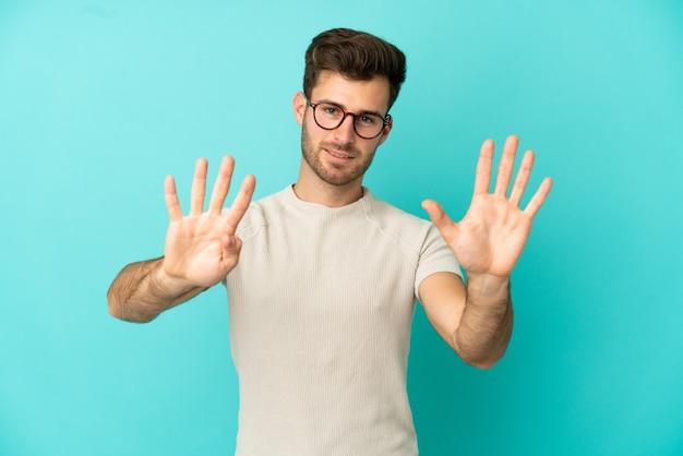 Jonge blanke knappe man geïsoleerd op blauwe achtergrond die negen met vingers telt
