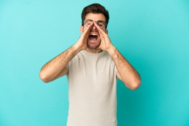 Jonge blanke knappe man geïsoleerd op blauwe achtergrond schreeuwen en iets aankondigen