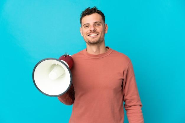 Jonge blanke knappe man geïsoleerd op blauwe muur met een megafoon en veel glimlachen