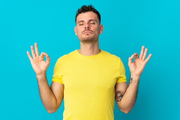 Jonge blanke knappe man geïsoleerd op een blauwe achtergrond in zen pose