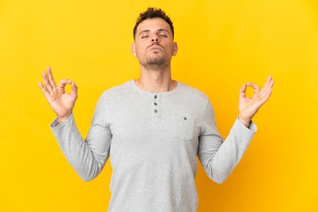 Jonge blanke knappe man geïsoleerd op gele achtergrond in zen pose
