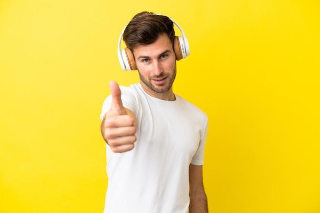 Jonge blanke knappe man geïsoleerd op gele achtergrond muziek luisteren en met duim omhoog
