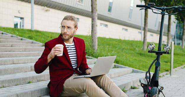 Jonge blanke knappe man in glazen en rode jas zittend op stappen buitenshuis, werken op laptopcomputer, drankje nippen. stijlvolle man koffie drinken. freelancer. elektrische scooter.