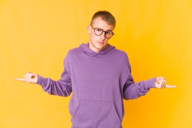 Jonge blanke knappe man twijfelende en schouders ophalen in vragend gebaar.