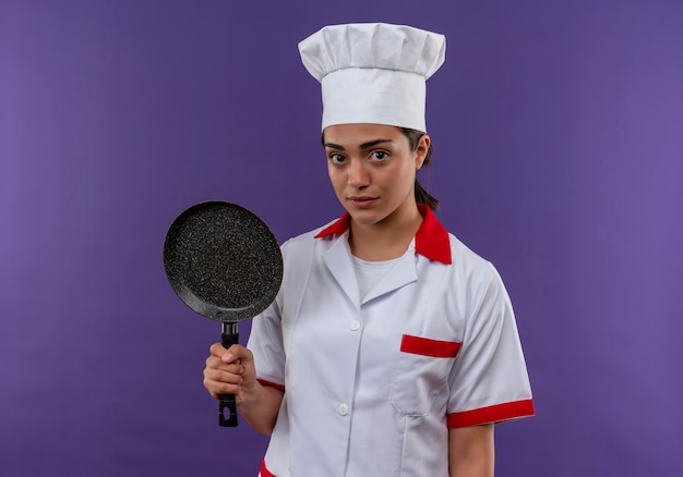 Jonge blanke kok meisje in uniform chef houdt koekenpan en kijkt naar camera geïsoleerd op violette achtergrond met kopie ruimte