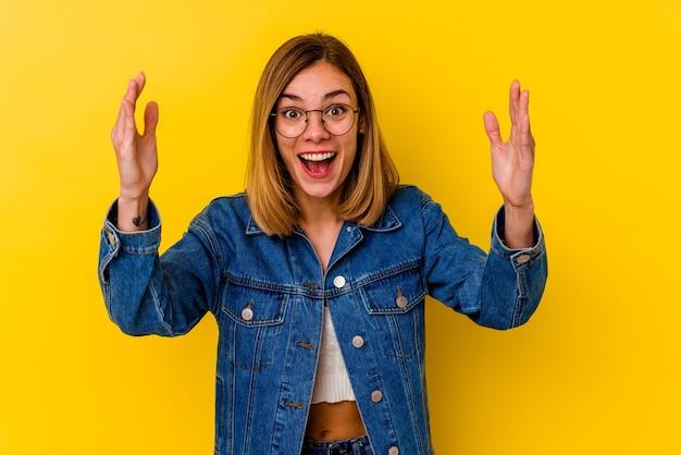Jonge blanke magere vrouw die op geel wordt geïsoleerd dat een aangename verrassing ontvangt, opgewonden en handen opheft.