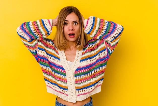 Jonge blanke magere vrouw geïsoleerd op geel bedekkende oren met handen proberen niet te hard geluid te horen.