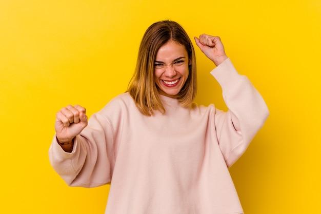 Jonge blanke magere vrouw geïsoleerd op geel dansen en plezier maken.