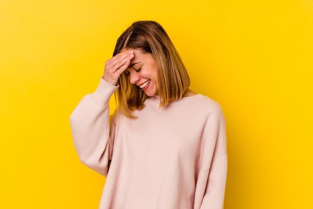 Jonge blanke magere vrouw geïsoleerd op geel knipperen door vingers, beschaamd bedekkend gezicht.