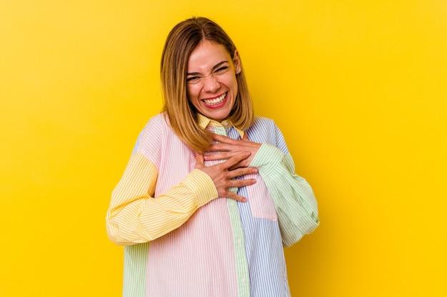 Jonge blanke magere vrouw geïsoleerd op geel lacht vrolijk en heeft plezier met het houden van handen op de buik.