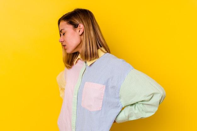 Jonge blanke magere vrouw geïsoleerd op geel met rugpijn.