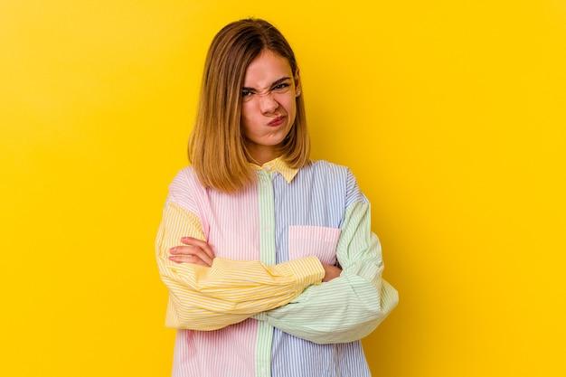 Jonge blanke magere vrouw geïsoleerd op geel ongelukkig frontaal kijken met sarcastische uitdrukking.
