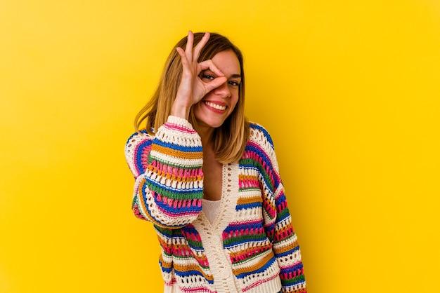 Jonge blanke magere vrouw geïsoleerd op geel opgewonden houden ok gebaar op oog.