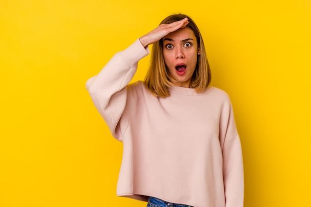 Jonge blanke magere vrouw geïsoleerd op geel schreeuwt luid, houdt ogen open en handen gespannen.