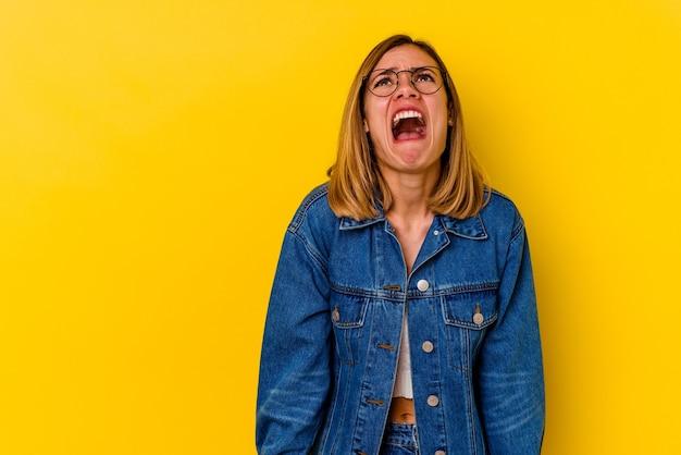 Jonge blanke magere vrouw geïsoleerd op gele achtergrond schreeuwen erg boos, gefrustreerd woedeconcept.