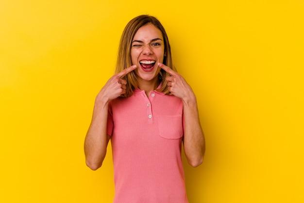 Jonge blanke magere vrouw geïsoleerd op gele muur glimlacht, wijzende vingers naar mond.