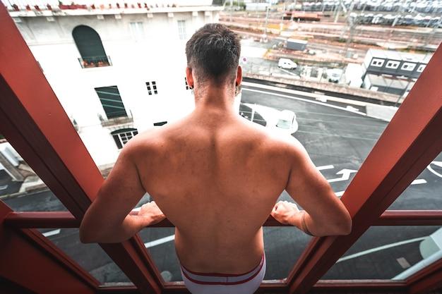 Jonge blanke man alleen met boksers op het terras van het appartement