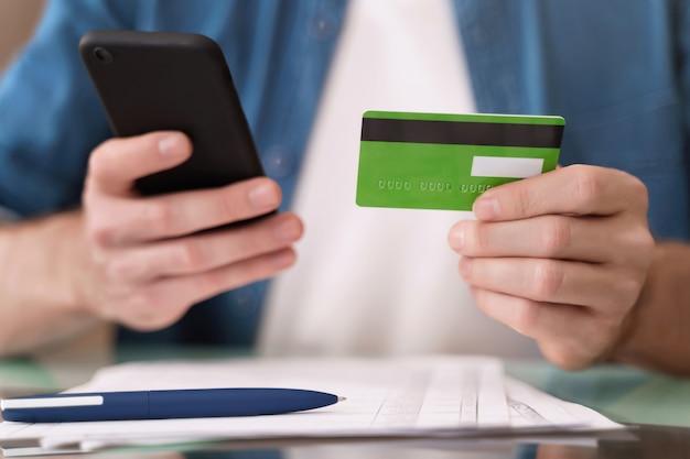 Jonge blanke man betalen van rekeningen online met smartphone thuis