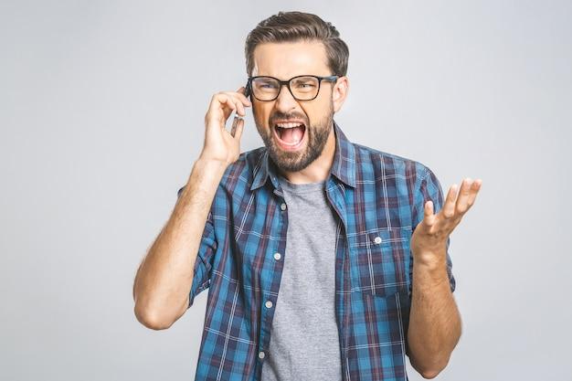 Jonge blanke man boos, gefrustreerd en woedend op zijn telefoon, boos op klantenservice. geïsoleerd.