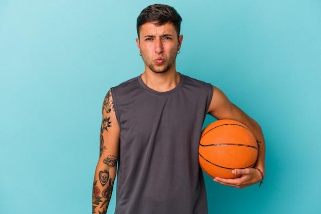 Jonge blanke man die basketbal speelt geïsoleerd op blauwe achtergrond haalt zijn schouders op en verwarde ogen.