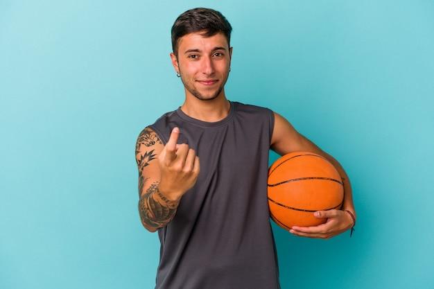 Jonge blanke man die basketbal speelt geïsoleerd op een blauwe achtergrond en met de vinger naar je wijst alsof uitnodigend dichterbij komt.