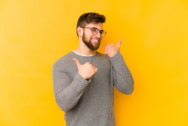 Jonge blanke man die beide duimen opheft, glimlachend en zelfverzekerd.