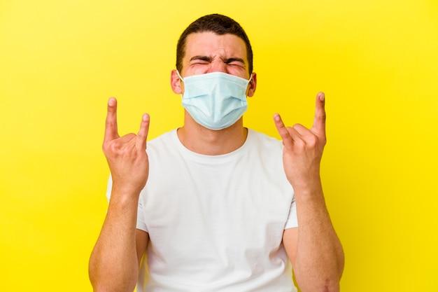 Jonge blanke man die een bescherming tegen coronavirus draagt die op gele achtergrond wordt geïsoleerd die rotsgebaar met vingers toont