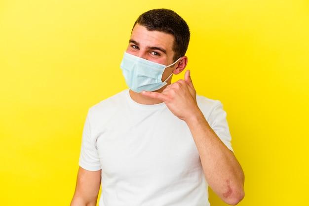 Jonge blanke man die een bescherming tegen coronavirus draagt die op gele achtergrond wordt geïsoleerd en een gebaar van een mobiel telefoongesprek met vingers toont.