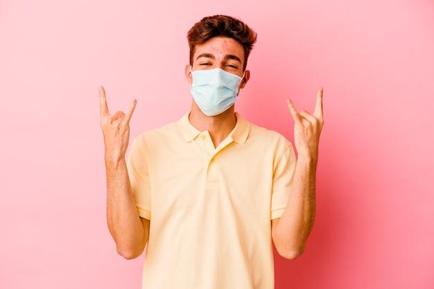 Jonge blanke man die een bescherming tegen coronavirus draagt die op roze achtergrond wordt geïsoleerd die rotsgebaar met vingers toont