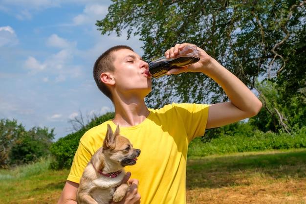 Jonge blanke man die een chihuahua-hond vasthoudt en buiten cola drinkt uit een fles. wandelen in het park in de zomer, lage kijkhoek